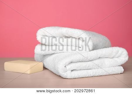 Clean towels on table against color background