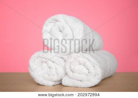 Rolled towels on table against color background