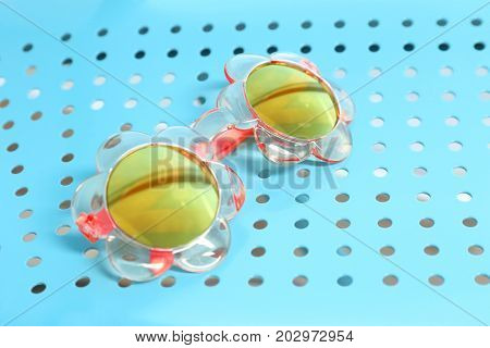 Beautiful sunglasses on color background