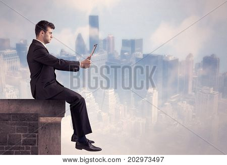 A young businessman sitting at the edge of a building in front of a city center scape background with tall buildings and clouds concept