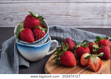 Red berry strawberry in ceramic mugs on old concrete background. Background from freshly harvested strawberries