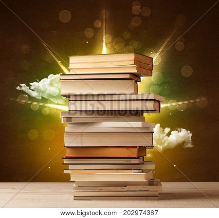 Magical books with ray of lights and colorful clouds on vintage background