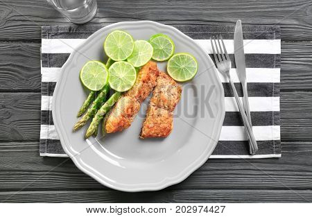 Plate with delicious salmon, sliced lime and asparagus on wooden table