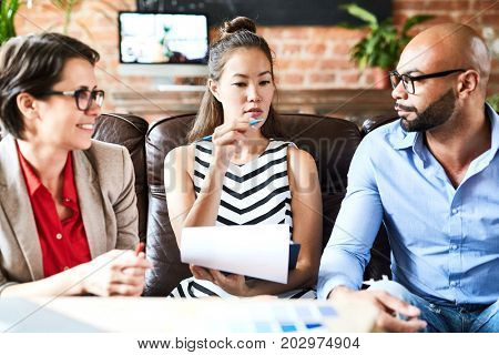 Confident Asian white collar worker with clipboard in hand sharing creative ideas concerning start-up project with colleagues