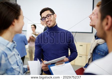 Young businessman talking to groupmates after seminar