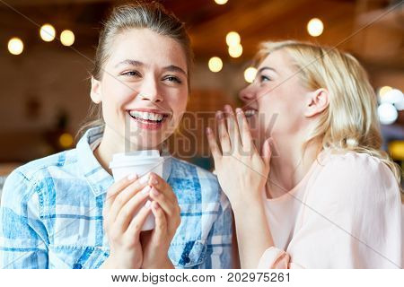 Attractive young woman sharing secret with cheerful friend while sitting at cozy small coffeehouse and enjoying fragrant cappuccino