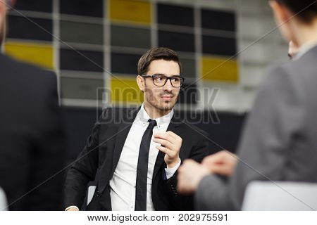 Serious professional listening to one of colleagues during start-up discussion