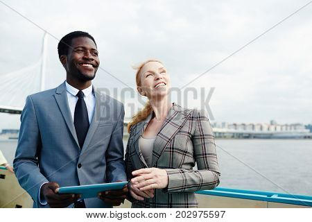 Successful professionals in formalwear enjoying trip by steamship