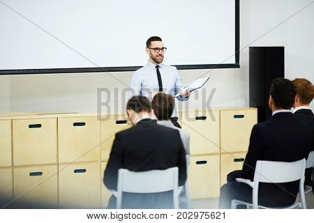Young coach carrying out master-class for attendants in auditorium