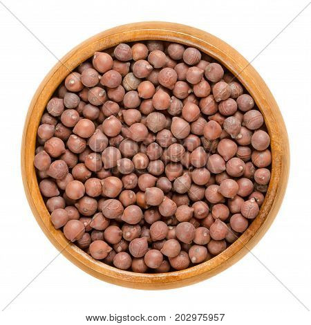 Desi chickpeas in wooden bowl. Dried brown seeds of Cicer arietinum, a legume. Also called Bengal gram, garbanzo bean or Egyptian pea. Macro food photo close up from above on white background.