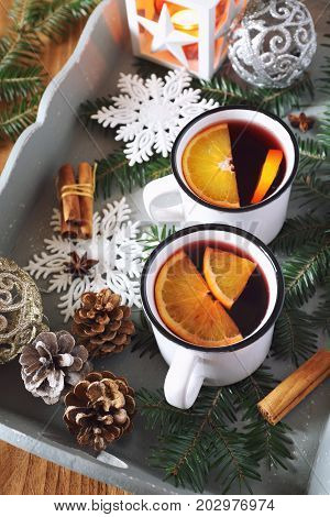 Mulled wine with spices and citrus fruit on vintage tray and burnind lantern