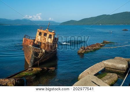 Small abandoned ship near the coast. Tilted rusty nautical longboat near the old pier.