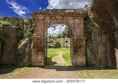 Ancient roman stone amphitheater main gate in the town of Sutri with clouds near Rome