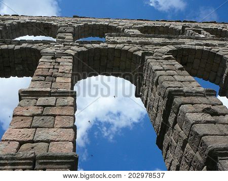Arches from Segovia aqueduct with blue sky and clouds