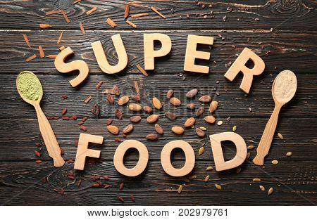 Composition with wooden letters and assortment of superfood products on table, top view