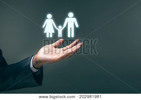 Insurance family concept Businessman is holding to take care and save family first. Business background.