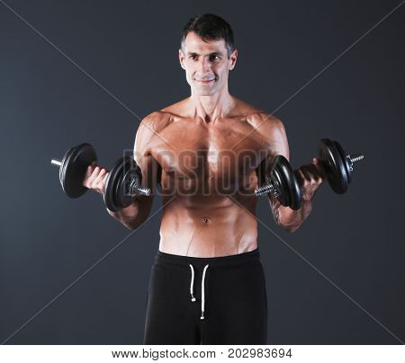 Handsome muscular man working out with dumbbells. Personal fitne
