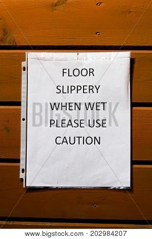 Floor slippery when wet use caution sign.