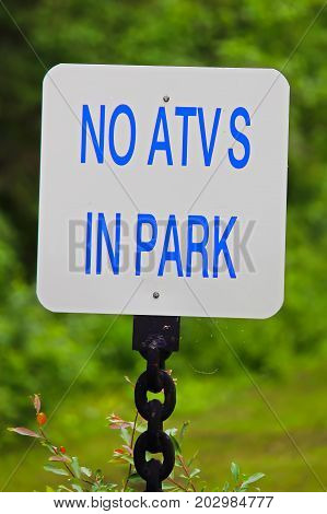A White No Atvs In Park Sign With A Green Background