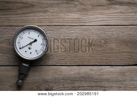 pressure gauge on wood background, top view