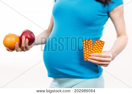 Pregnant Woman Holding Fresh Ripe Fruits And Medical Pills Or Supplements, Choice Between Healthy Fo