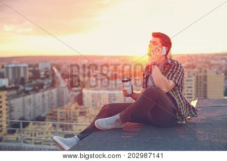 A hipster man drinks coffee and talks on his cell phone. He sits on the roof of a high-rise building at sunset. Portrait in the rays of the setting sun