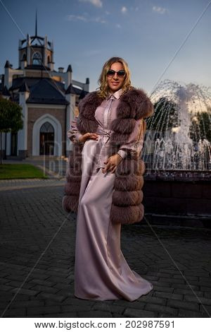 Attractive woman in pink lady's fur coat in front of fountain