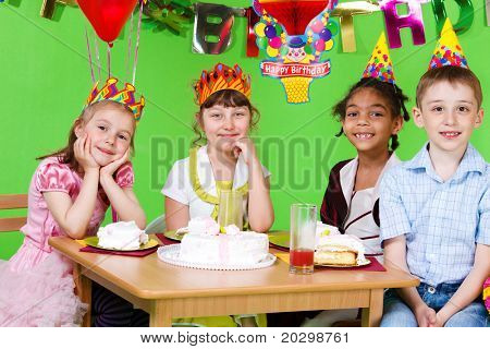 Sweet friends sitting at the table and eating  birthday cake