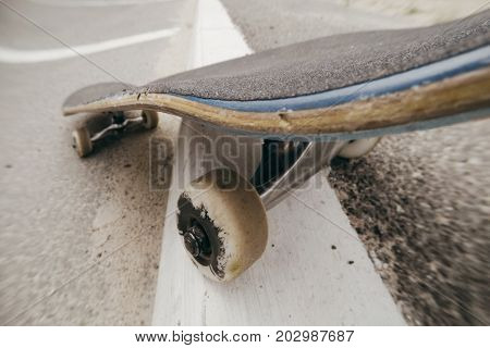 Close up of moving skateboard on city road marking. Extreme sport challenge, tricks and skateboarder training, urban lifestyle and adventures