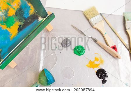 Creative painter workplace top view. Art studio. Interesting hobby for children, craft tools. Abstract painting, artistic concept
