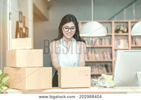 Young Entrepreneur Packing Product Into The Box For Her Customers After Received Order At Home Offic
