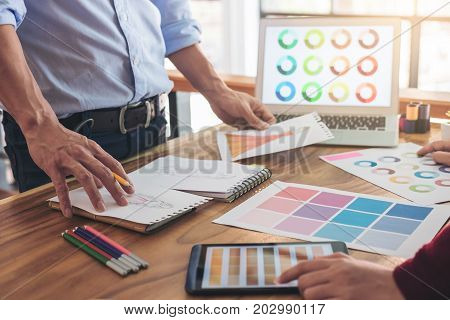 Two young professional Fashion designer colleagues working and project of drawing sketches for clothes in workplace with laptop digital tablet and color charts Fashion Designer Stylish Concept.
