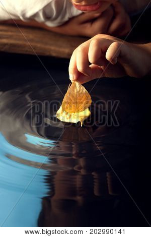 boy play with leaf ship in water (focus on ship)
