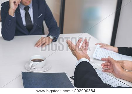 Interviewer or Board reading a resume during a job interview Employer interviewing a young male job seeker for recruitment talking in modern office employment and recruitment concept.