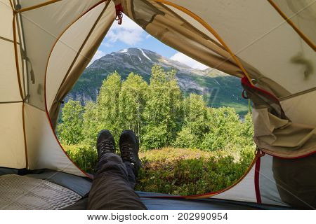 View of the Norwegian mountains from a tourist tent in a camping. Guy in trekking boots