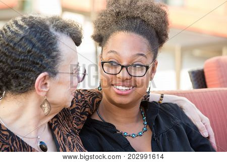 Closeup portrait granddaughter and grandmother sitting having deep conversation looking at each other isolated outdoors background