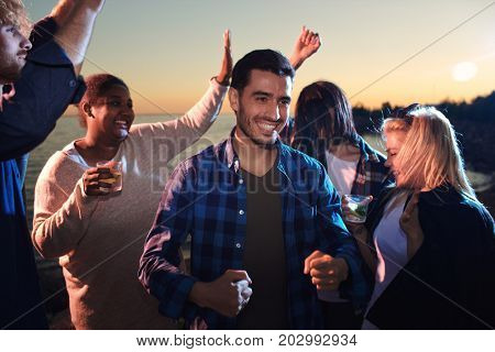 Ecstatic guys and girls dancing in the dusk on the beach