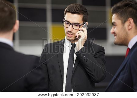 Ambitious professional speaking by smartphone with two colleagues near by