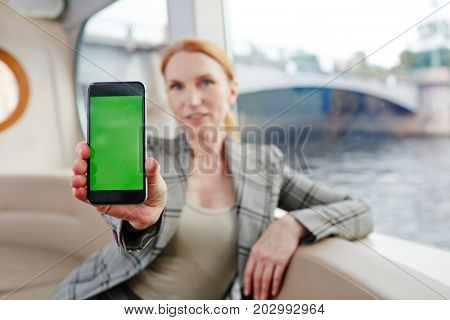Posh businesswoman stretching her hand with smartphone and showing online offer