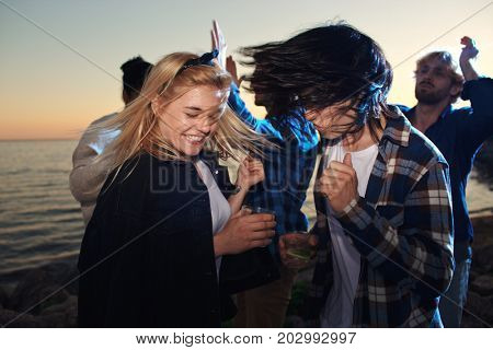 Young intercultural couple dancing by seaside with their friends on background