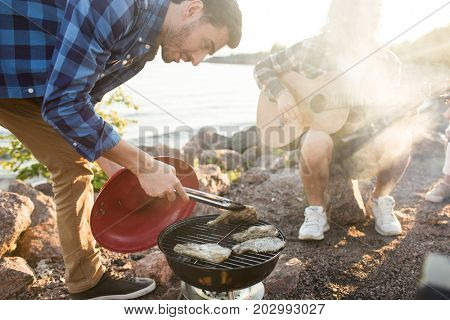 Young man roasting meat on barbecue grill during get-together with friends