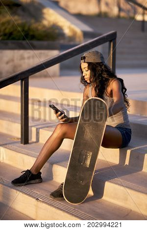 african american woman in skatepark with skateboard using smart phone on steps