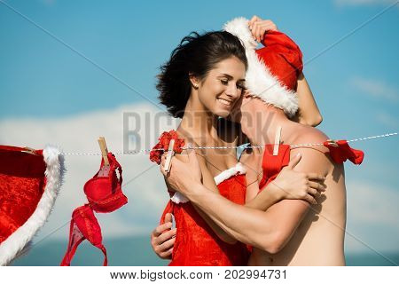 Xmas red costume on rope with pin. Laundry and dry cleaning. Christmas man and woman. New year guy with muscular body on blue sky. Couple in love of man and happy girl hanging clothes for drying.