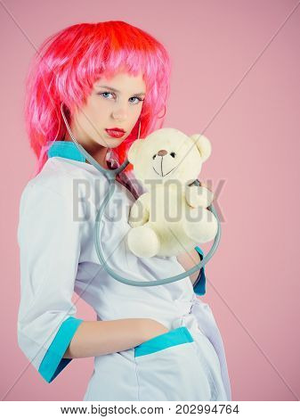Girl examining teddy bear toy with stethoscope. Nurse on pink background. Health care and cure concept. Doctor and patient. Woman wearing medical uniform and red wig.