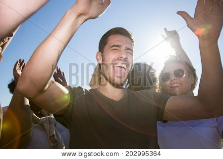 Ecstatic guy laughing while deancing among his friends on sunny day