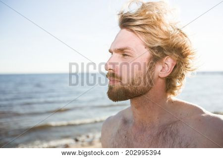 Restful young man enjoying solitude by seaside on summer evening