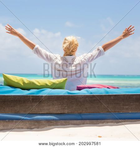 Relaxed woman in luxury lounger, arms rised, enjoying summer vacations on beautiful beach. Lady feeling free, relaxed and happy. Concept of vacations, freedom, happiness, enjoyment and well being.