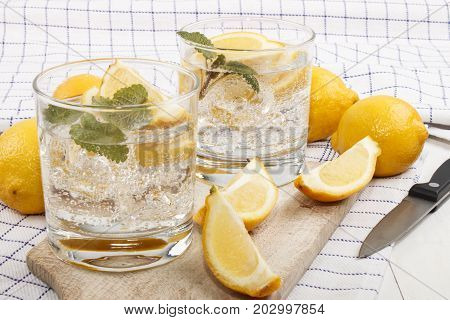 cold mineral water with lemon as a refreshing drink in a glass