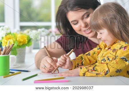 Portrait of mother and daughter drawing picture