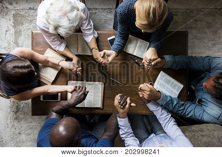 Group of people holding hands praying worship believe